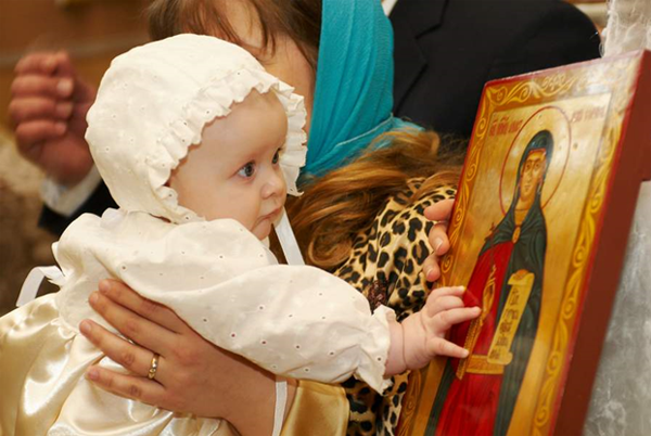 младенец рядом с иконой