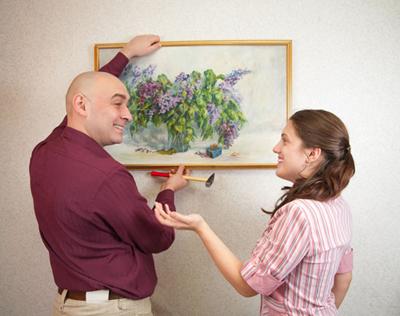 мужчина вешает подаренную картину